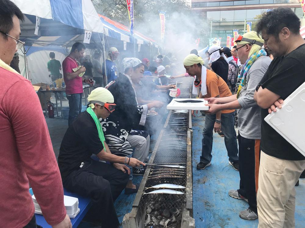 長い焼き台の上にずらりと並べられ次々と焼かれる秋刀魚